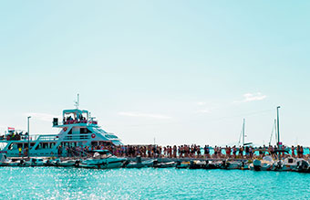 Festivalgoers queuing for a yacht at a jetty